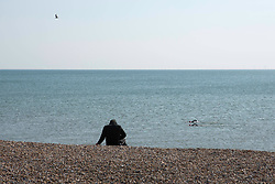 A person sunbathes on the beach as swimmers pass by in Brighton, East Sussex, as the UK continues in lockdown to help curb the spread of Coronavirus.