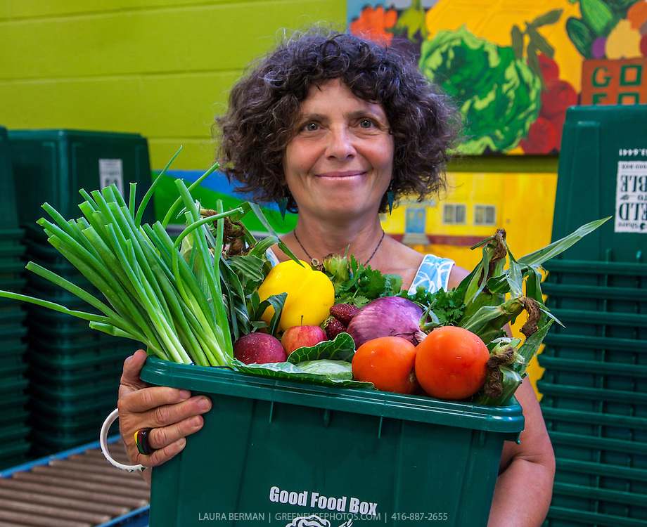 FoodShare's Executive Director Debbie Field,  holds a Good Food Box in FoodShare's warehouse.
