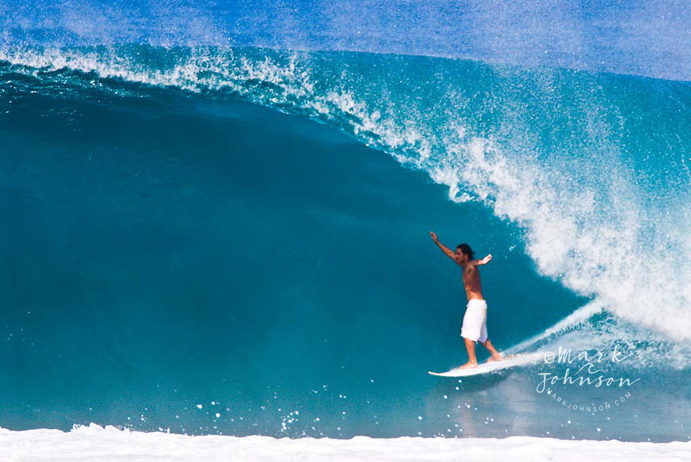 Surfer with arms upraised, in the tube at Backdoor Pipeline, North Shore, Oahu, Hawaii
