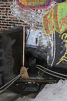 Broom resting against grafitti covered rooftop wall in DUMBO Brooklyn New York