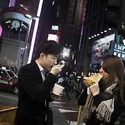 """A young and trendy couple eat street food in Time's Square shortly before Christmas. <br /> <br /> Hong Kong (香港; """"Fragrant Harbour""""), officially known as Hong Kong Special Administrative Region of the People's Republic of China since the hand-over from the United Kingdom in 1997 under the principle of """"one country, two systsems"""".  7 million people live on 1,104km square, making it the most vertivcal city in the world. Hong Kong is one of the world's leading financial centres along side London and New York, it has one of the highest income per capita in the world as well the moste severe income inequality amongst advanced economies. The Hong Kong civil society is highly regulated but has at the same time one of the most lassiez-faire economies with low taxation and free trade. Civil unrest and political dissent is unusual but in 2014 the Umbrella Movenment took to the streets of Hong Kong demanding democracy and universal suffrage. 93 % are ethnic Chinese, mostly Cantonese speaking."""