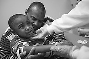 Quadir is reassured by a nurse as she draws blood for pre-op tests at University Hospital, UMDNJ.  His father Kevin Rahman Hutchins holds him tight.