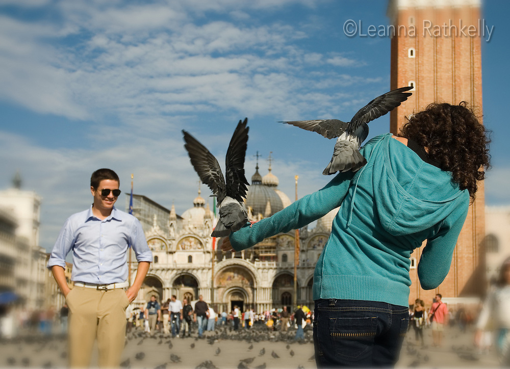 Girl, 14, feeds the pigeons in Piazza San Marco, Venice, Italy. Basilica in background