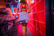 "21 JANUARY 2013 - BANGKOK, THAILAND:  A sex worker leaves a ""short time hotel"" near the Nana Entertainment Plaza, a red light district in Bangkok. Prostitution in Thailand is technically illegal, although in practice it is tolerated and partly regulated. Prostitution is practiced openly throughout the country. The number of prostitutes is difficult to determine, estimates vary widely. Since the Vietnam War, Thailand has gained international notoriety among travelers from many countries as a sex tourism destination. One estimate published in 2003 placed the trade at US$ 4.3 billion per year or about three percent of the Thai economy. It has been suggested that at least 10% of tourist dollars may be spent on the sex trade. According to a 2001 report by the World Health Organisation: ""There are between 150,000 and 200,000 sex workers (in Thailand).""  PHOTO BY JACK KURTZ"