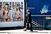 A man stares at an ad with two girls on a street of Tribeca in Manhattan, New York, 2008.