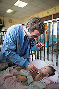Dr. Jamie Penk, Intensivist/Cardiologist examines patient Fany - AV Canal Complete Repair - in the pediatrics ward prior to her surgery. Baby Heart Medical Mission to Honduras.