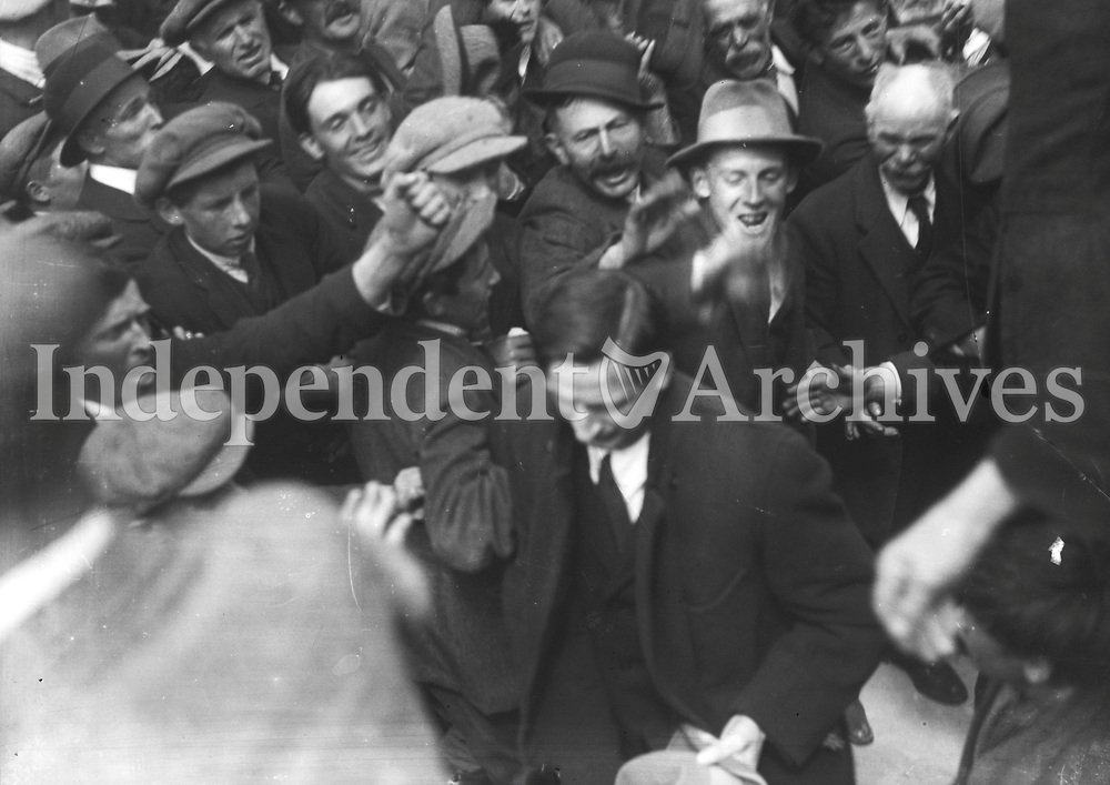 IND_H_0556<br /> <br /> Eamon De Valera arrest at Ennis. De Valera being cheered by crowds. 15th August 1923<br /> <br /> <br /> <br /> During the Civil War of 1922-1923 between the pro-Treaty Provisional Government under Michael Collins and its opponents, Eamonn de Valera supported the anti-Treaty Republicans. An &euml;Emergency Government&iacute; was formed by the Republicans with de Valera as president. In May 1923 the Republicans called a cease fire and resistance ended. De Valera was arrested on 15 August 1923, under the Public Safety Act, as he was about to make a speech at Ennis and was imprisoned until July 1924. Despite this, Clare elected de Valera top of the poll in the general election on 27 August 1923. Eamonn de Valera continued to represent Clare for the rest of his active political career.<br /> <br /> http://clarelibrary.blogspot.com/2010/07/eamonn-de-valera-arrested-in-ennis-film.html Part of the NPA/Independent Collection (Part of the Independent Newspapers Ireland/NLI Collection)
