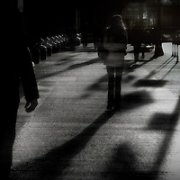 Silhouetted figures walking along a street