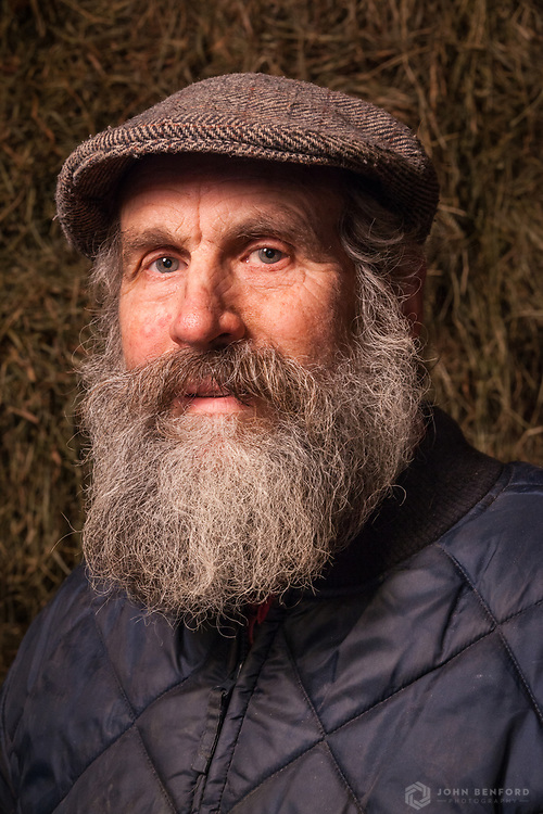 A head shot portrait of a farmer with a full salt & pepper beard against bales of hay.