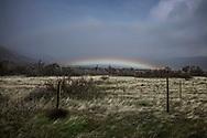 A rainbow hugs a desert valley entering the Anzz-Borrego Desert near Scissors Crossing.  California.