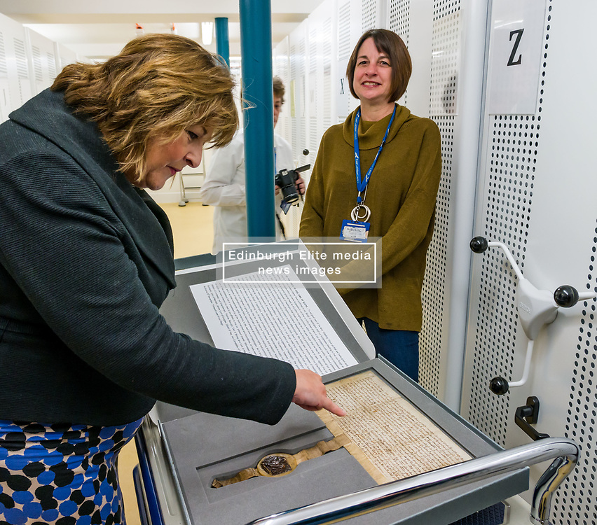 Pictured: Scottish Government Public Libraries Funding Announcement. Culture Minister Fiona Hyslop announces this year's successful bids to the £450,000 Public Library Improvement Fund (PLIF) at the John Grey Centre, Haddington Library, Haddington, East Lothian, Scotland, United Kingdom.  PLIF has been supporting innovative library projects since 2006 which help both individuals and communities. Fiona Hyslop visits the archives of East Lothian to see Haddington's 700 year old charter from Robert the Bruce, the anniversary of which is being celebrated this year,. Pictured: Fiona Hyslop and Ruth Fyfe, archivist. 13 December 2018  <br /> <br /> Sally Anderson   EdinburghElitemedia.co.uk