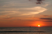 An image of a beautiful Hawaiian sunset with a sailboat.