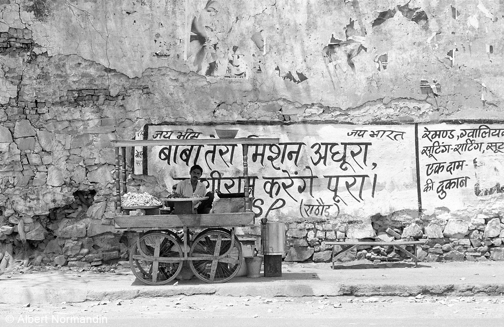 Vendor on side of road with cart and signage