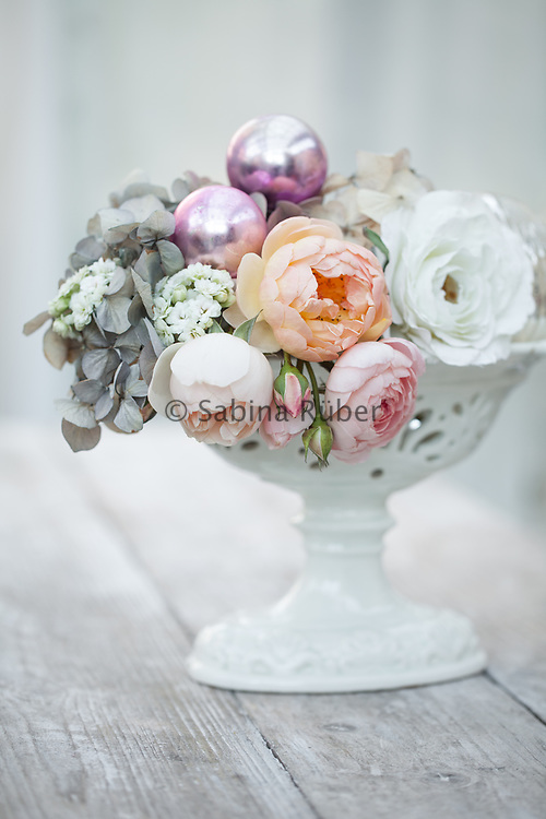 Still life with English roses, Hydrangea, Kalanchoe and glass baubles in white, antique vase
