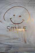 A happy, optimistic smiley hand-drawn on a whitewashed window of a soon-to-open cafe in central London.