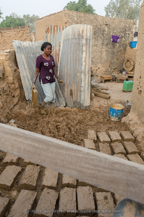 Fati Koanda (40), seen on 24 February 2016, is making mud bricks by hand to build a more permanent structure to replace the makeshift zinc sheet wash room seen behind her at her home in Zongo, an informal settlement in Burkina Faso's capital, Ouagadougou. She has a separate latrine, which was built under a WaterAid supported program. She is a widow, and lives with her 17 year-old daughter, Safiatou Kafando.