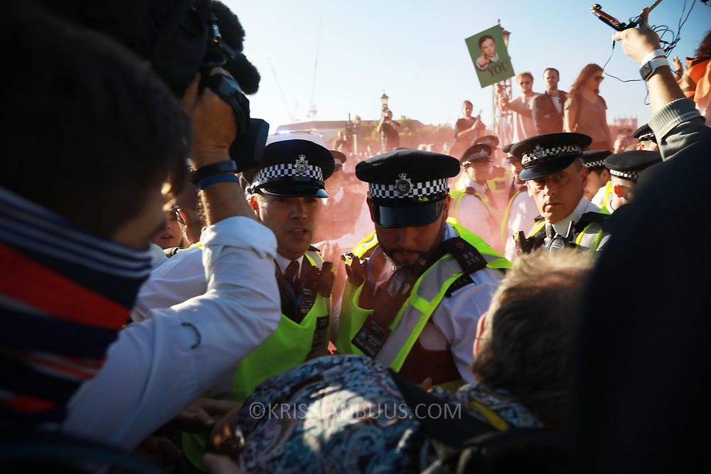 Tens of thousands took to the streets in Central London taking part in the the Global Climate Strike, September 20th 2019, London, United Kingdom.  A protester is arrested for lighting a red flare. For a short while Lambeth Bridge was occupied by sitting protesters, most of them teenagers. The Police quickly cleared the bridge and opened it up to traffic again. The day of strike for the climate was a global event with millions taking part across the globe. The strike was inspired by Greta Thunberg, a Swedish school girl who started the first school strike for the climate. Her action inspired school children across the world to go on strike demanding radical climate change policies to save their future. On September 20th adults aand children alike went out on strike to demand radical political change and climate justice. The day included speeches and a march through central London.