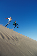 Two young men jumping off sand dune ridge; Oregon Dunes National Recreation Area, Umpqua Dunes section, Oregon coast.  .