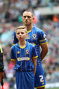 Barry Fuller (Captain) defender for AFC Wimbledon (2) with a mascot before the Sky Bet League 2 play off final match between AFC Wimbledon and Plymouth Argyle at Wembley Stadium, London, England on 30 May 2016. Photo by Stuart Butcher.