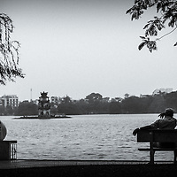 Locals do early morning exercises and catch up the news at Hoan Kiem lake, Hanoi, Vietnam
