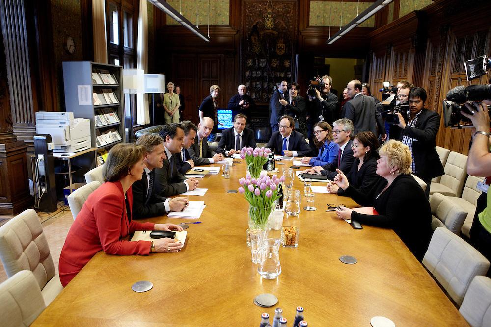 Nederland. Den Haag, 26 april 2012. <br /> Rond zeven uur komen de vertegenwoordigers van de vijf partijen met minister De Jager van financien bijeen in de fractiekamer van D66 (waar ze deze dag hebben onderhandeld) om het akkoord te bezegelen.<br /> Fractievoorzitters Van Haersma, (CDA), Blok (VVD), Pechtold (D66), Slob (CU). En Sap van GroenLinks met hun resp. financieel specialisten.<br /> VVD, CDA, D66, GroenLinks en ChristenUnie zijn met het kabinet een principe-akkoord overeengekomen over de begroting van volgend jaar.<br /> Men is als Tweede Kamer uit de impasse gekomen om voor mei een begroting voor 2013 op te stellen na de val van het kabinet Rutte van VVD, CDA en met gedoogsteun van de PVV van Geert Wilders. Crisisakkoord na mislukken ook van Catshuisberaad. 3% Financieringstekort.<br /> Het kabinet en de regeringspartijen VVD en CDA hebben in twee politiek gezien krankzinnige dagen met de oppositiepartijen D66, GroenLinks en de ChristenUnie een akkoord gesloten over bezuinigingen en hervormingen in 2013. Minister Jan Kees de Jager van Financi&euml;n koppelde als verkenner de vijf partijen aan elkaar en kreeg in nog geen 30 uur voor elkaar waar VVD en CDA met gedoogpartij PVV in 7 weken overleg in het Catshuis niet in waren geslaagd. Politiek, kabinet Rutte, kabinetscrisis, Catshuisonderhandelingen, Tweede Kamer, <br /> Foto : Martijn Beekman