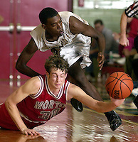 Morton forward Ben Smidt and Manual forward Bryan Stewart battle for a loose ball at Lincoln High School. High School basketball games in Illinois are community events and well-attended.