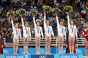 17 August 2004: The Romanian Team celebrate on the podium after winning the Gold medal in the Women's Artistic Gymnastics Team Final in the Olympic Indoor Hall at the 2004 Olympic Games, Athens, Greece. <br />