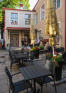 Tallin, Estonia -- July 23, 2019. A vertical wide angle shot of a restaurant outdoor dining area in Tallin, Estonia.  rising in the background.