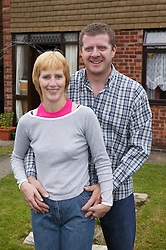 Man and woman standing outside house together,