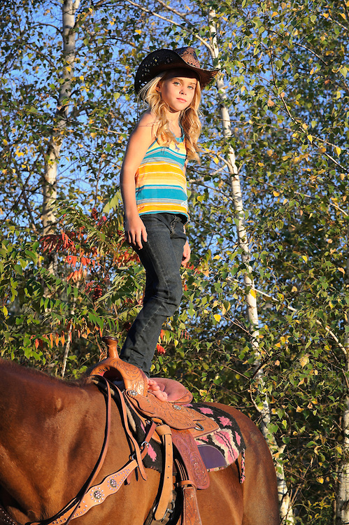 Young blonde cowgirl standing tall on her horse saddle showing off a horsemanship trick with good steady balance, Pennsylvania, PA, USA.