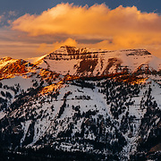 A clearing winter storm gives way to a vivid mountain sunset over Rendezvous Peak in Bridger-Teton National Forest.