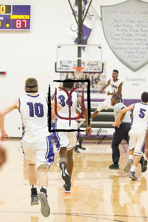 The Cedar Ridge basketball team celebrates an overtime win against San Marcos November 21, 2014 at Cedar Ridge Gym.