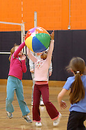 Middletown, N.Y. - Two7-year-old girls reach for a beach ball at the volleyball station during National Women in Sports Day on Feb. 11, 2006. Orange County Community College's Department of Movement Science celebrated the 20th Anniversary of National Girls and Women in Sports Day by holding an event for young girls that included volleyball, basketball, soccer, games and swimming.