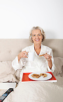 Portrait of happy senior woman having breakfast in bed