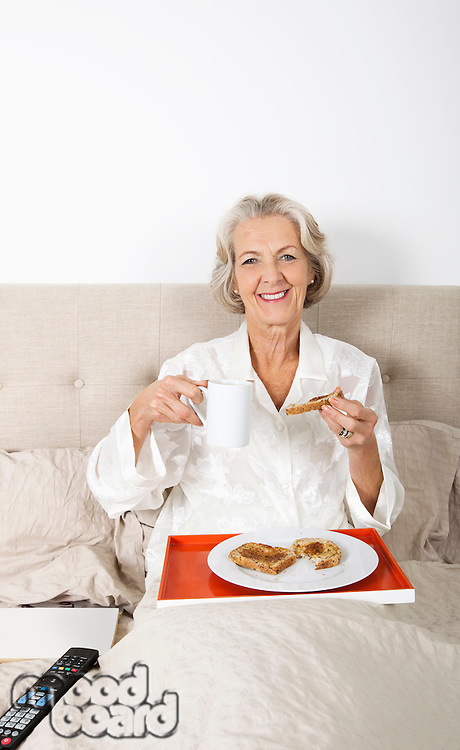 Portrait of happy senior woman having breakfast in bed