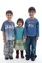 Portrait of three children smiling in the studio,