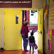 WASHINGTON, DC - APR 24:  A mom drops off her daughter at Simon Elementary School in Washington, DC, under a banner encouraging school attendance, April 24, 2014. DC has enormous truancy rates, even among young children. In the last year or two, the school system has made a big push to improve attendance. Simon Elementary is seen as a model, introducing incentives and games that are tied to attendance and meant to get kids excited about coming to school; systems to ensure that parents get a call home whenever their kids are absent; weekly attendance meetings to talk about kids who are missing too much school; and a partnership with a community based organisation that can make home visits and connect families with services. (Photo by Evelyn Hockstein/For The Washington Post)