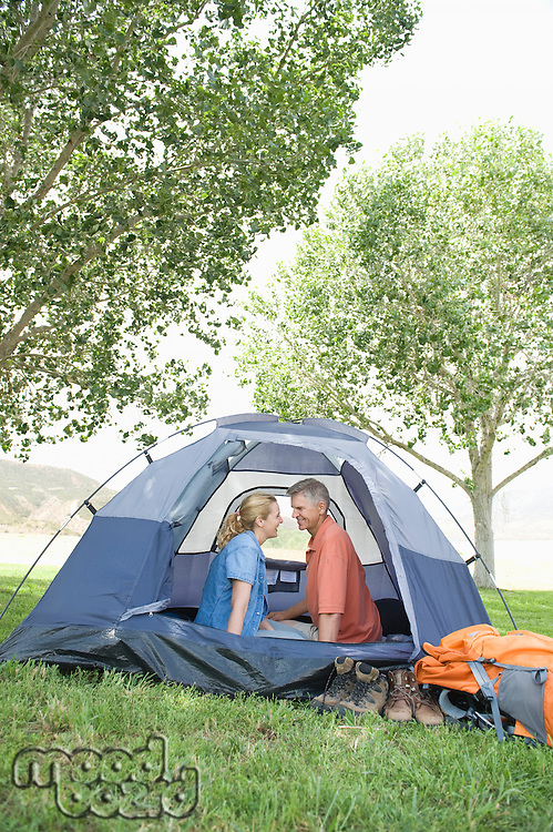 Mature couple sit face to face in tent