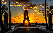 The sun rises behind the Worth Avenue clock tower into partly cloudy skies