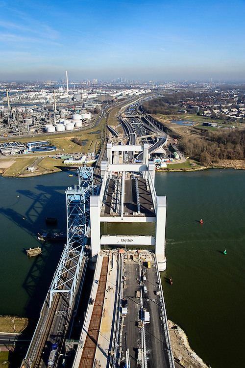 Nederland, Zuid-Holland, Rotterdam, 18-02-2015; bouw van de nieuwe Botlekbrug.<br /> De brug over de Oude Maas is een hefbrug, een van de twee brugdelen in geheven toestand. Links de oude brug, raffianderij van Shell Pernis in de achtergrond.<br /> Construction of the new Botlek bridge.<br /> The bridge over the Oude Maas is a vertical-lift bridge or lift bridge, one of the two bridge sections raised. <br /> luchtfoto (toeslag op standard tarieven);<br /> aerial photo (additional fee required);<br /> copyright foto/photo Siebe Swart