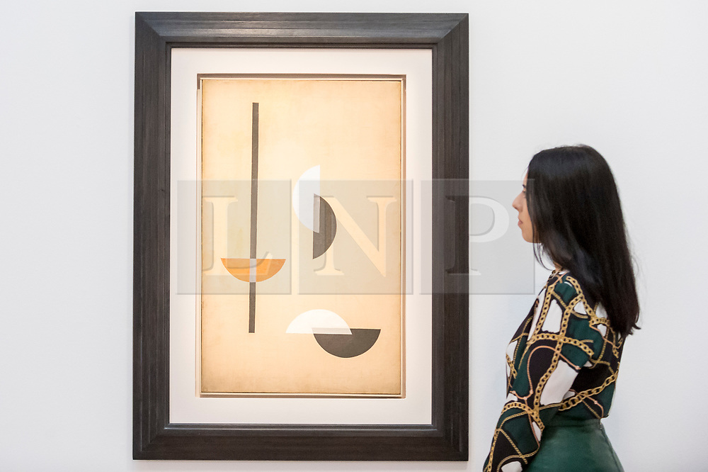 "© Licensed to London News Pictures. 20/02/2019. LONDON, UK. A staff member views ""Segments"", 1921, by László Moholy-Nagy, (Est. £0.3-0.5m). Preview of Sotheby's Impressionist & Modern and Surrealist Art sales.  The auction will take place at Sotheby's New Bond Street on 26 February 2019.  Photo credit: Stephen Chung/LNP"