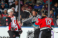 KELOWNA, BC - NOVEMBER 30: Connor Bowie #21 of the Prince George Cougars trash talks Jadon Joseph #18 of the Kelowna Rockets at the face off as linesman Mike Roberts intervenes at Prospera Place on November 30, 2019 in Kelowna, Canada. (Photo by Marissa Baecker/Shoot the Breeze)