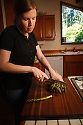 USA, Oregon, Eugene, young woman chopping asparagus for dinner. MR