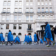 November 1, 2015 - New York, NY : Runners wearing their post-race blue hooded capes, walk along Central Park West on the Upper West Side following the 2015 TCS New York City marathon on Sunday.<br />