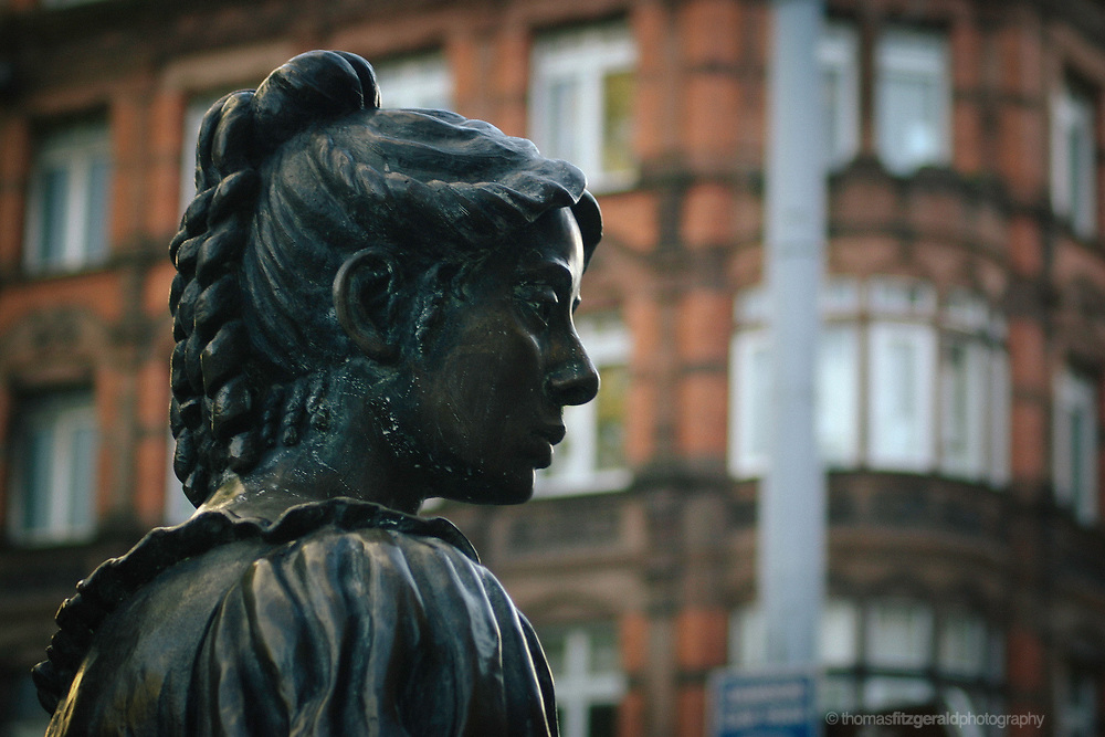 A close up of the iconic Molly Malone statue that is a feature of Dublin City. In the background is the out of focus redbrick street scape of Dublin's Grafton Street