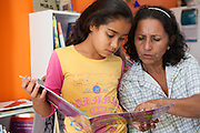 Giovana looks at a book with Neusa who works full time at the community library, Biblioteca Comunitaria do Arquipelago, Porte Alegre, Brazil. <br /> <br /> Cirandar is working in partnership with  C&A and C&A Instituto to implement a network of Community Libraries in eight communities of Porto Alegre.