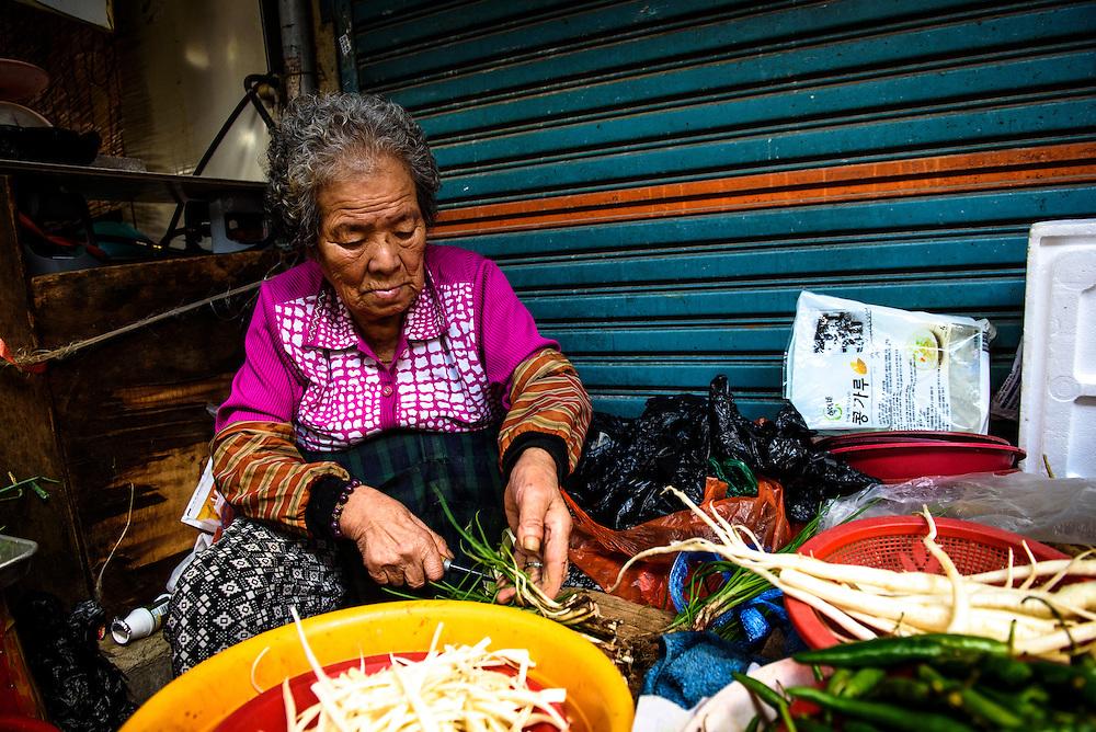 A woman prepares produce for sale at Oncheongjang Market in Busan, South Korea