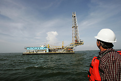 "An offshore oil drilling rig sits on Lake Maracaibo.  Since the removal of nearly 18,000 workers after an oil strike in Venezuela in 2002, PDVSA, the state run oil company has gone through drastic changes.  Struggling to replace the dismissed workers and return production to pre-strike quantities, PDVSA has also undertaken the financing and coordination of huge social programs.  PDVSA has invested billions of dollars in various education, food, medicine and infrastructure projects, calling itself the ""new"" PDVSA."