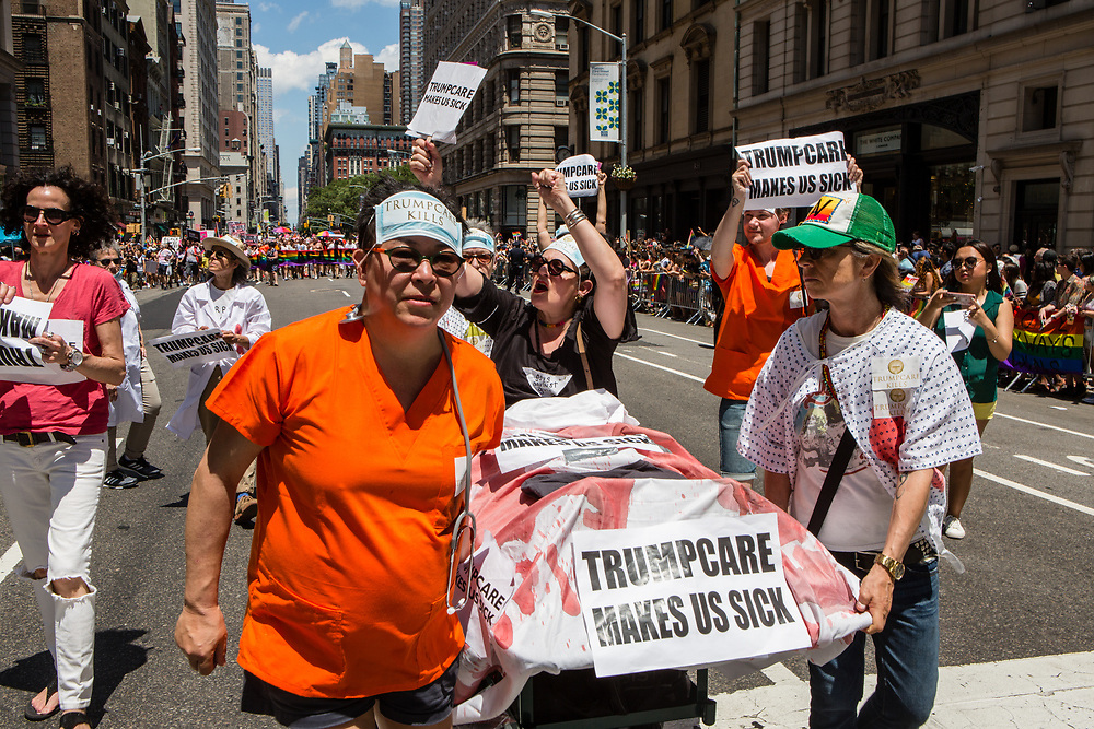 """New York, NY - 25 June 2017. New York City Heritage of Pride March filled Fifth Avenue for hours with groups from the LGBT community and it's supporters. People dressed as hospital attendants wheel a hospital bed carrying a patient, with signs that read """"Trumpcare makes us sick."""""""