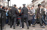 Police lead a protester away in handcuffs through tourists